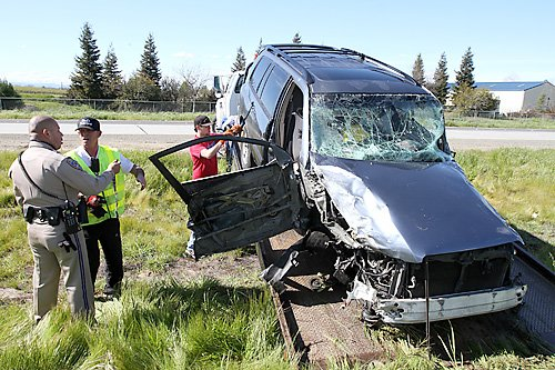 A California Highway Patrol officer speaks with a Bud's Towing employee regarding the Toyota Highlander they are towing from a fatal accident that occurred on Highway 113 near the Gibson Road exit. Fred Gladdis/Enterprise photo