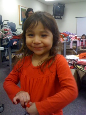 A new red shirt prompts a big smile from this little girl, one of 300 Yolo County infants and children who received new clothing, shoes and accessories donated last month by Gymboree Corp. last month.