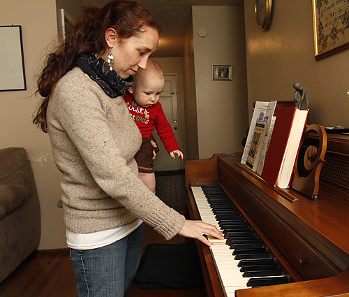 Sarah Majorins works out a melody on the piano with 9-month-old son Manny on her hip. The busy mom of 2-year-old Rachel and 3-year-old Trinity specializes in composing music for special occasions. Fred Gladdis/Enterprise photo