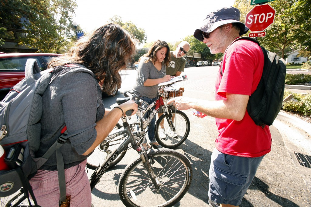John Whitehead of Davis Bicycles!, right, gives free bike lights to Marlene Amador and Melissa Franco, both third-year chemistry majors at UC Davis, during a promotion in downtown Davis during the last week of September. More lights will be distributed Saturday at the Davis Farmers Market. Fred Gladdis/Enterprise file photo