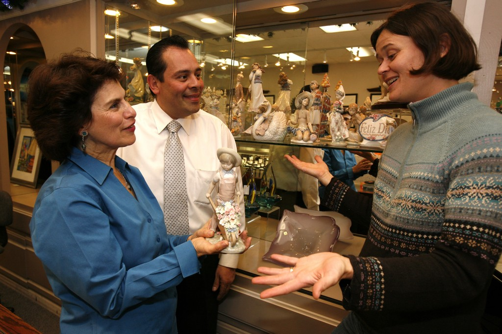 "St. James Parish volunteers Jeannette Newman-Velez, left, holding a Lladró ceramic sculpture — ""Wheelbarrow with Flowers"" by Francisco Catalá — and Nicole Rabaud discuss the Narcissa Peña collection with Frank Acosta, owner of 3rd Street Jeweler. Fred Gladdis/Enterprise photo"
