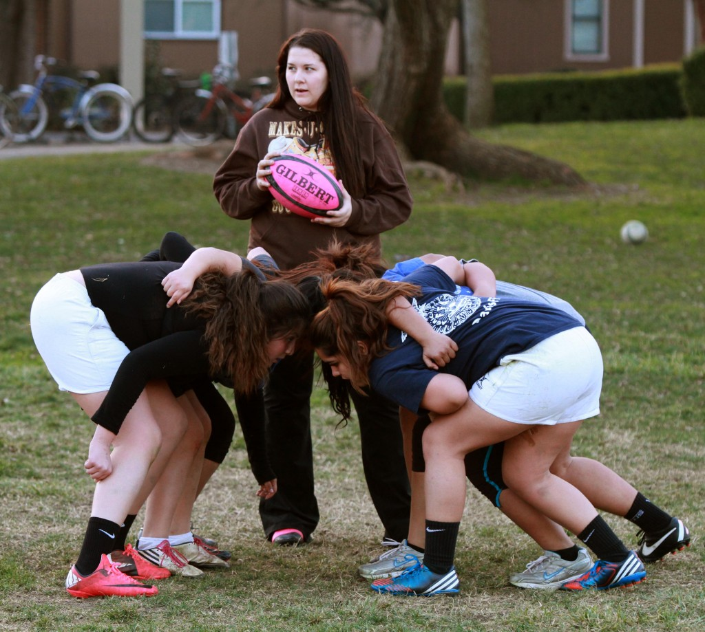 Lady Devils rugby coach Jordan Apodaca, a former player for the club, watches some of her girls gather for a scrum at a recent practice. Fred Gladdis/Enterprise photo