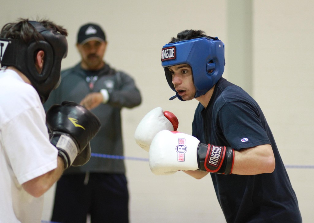 UCD club boxer Colin Schmitt, right, spars with a teammate during a recent practice. Coach Hector Lopez, a Davis High graduate, is in the background. Fred Gladdis/Enterprise photo