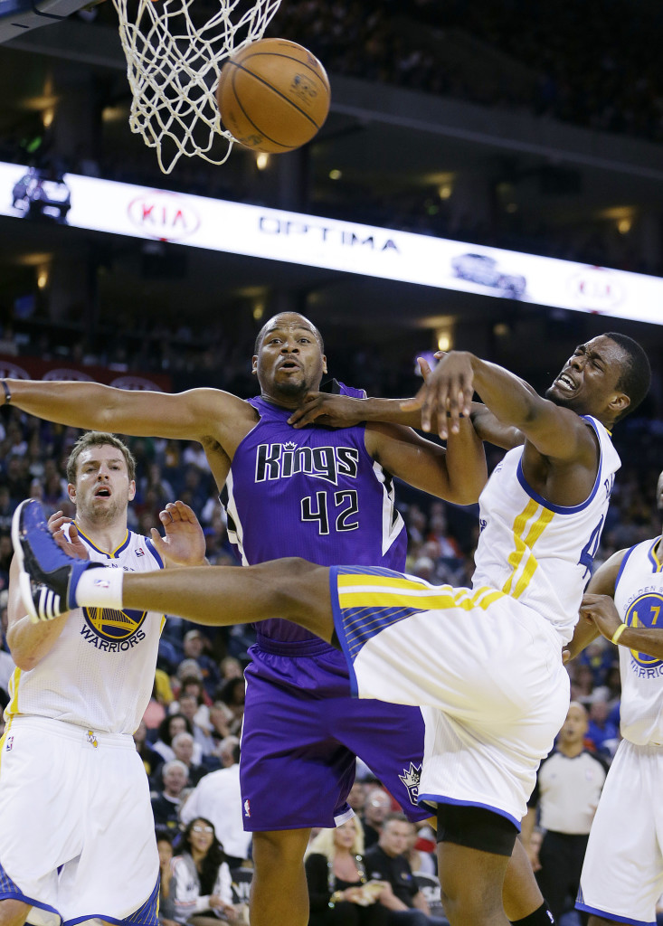 Sacramento's Chuck Hayes (42) and Golden State's David Lee, left, and Harrison Barnes compete for a loose ball in the Kings' 105-98 win over the Warriors on Thursday. AP photo