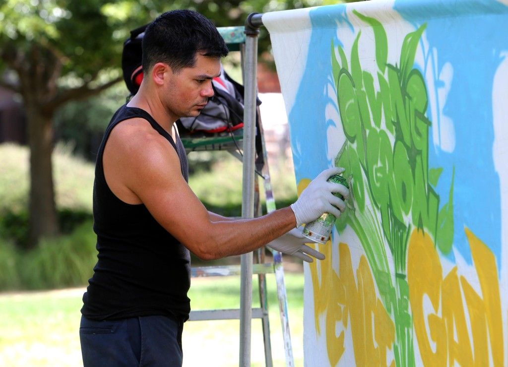 Anthony Padilla creates a mural for the Pence Gallery on Monday at Davis Commons. Sue Cockrell/Enterprise photo