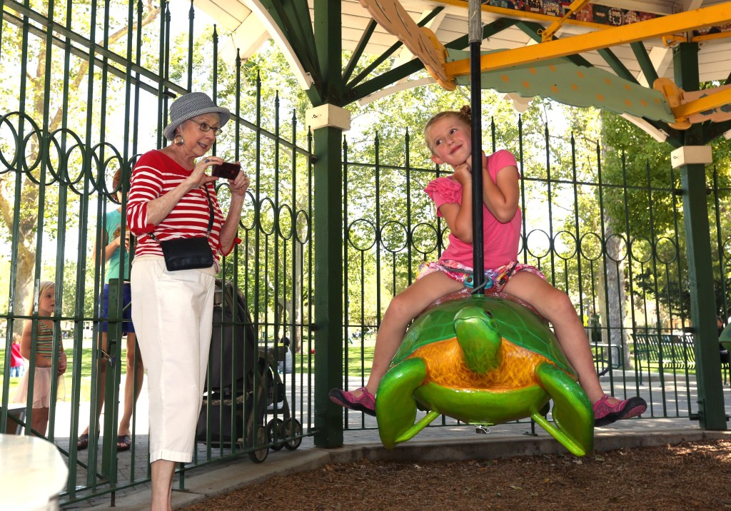 Linda Brant takes pictures of her grand daughter Kate Peres, 5, as she takes a spin on the new sea turtle on The Flying Carousel of the Delta Breeze. The turtle joined the pedal-powered ride thanks to a family donation in honor of Rachel Brant Peres, Evan and Kate's mother, who died of cancer last year. Fred Gladdis/Enterprise photo