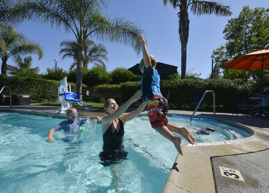Does your family need a getaway but you're not interested in the stress and expense of travel? Try vacationing right here in Davis, where local hotels, restaurants, shops and services can provide a luxurious and relaxing experience. Here, Angie Purves and her boys Sam, 3; Tommy, 5; and George, 8; enjoy splashing around in the swimming pool at the University Park Inn & Suites. Wayne Tilcock/Enterprise photo