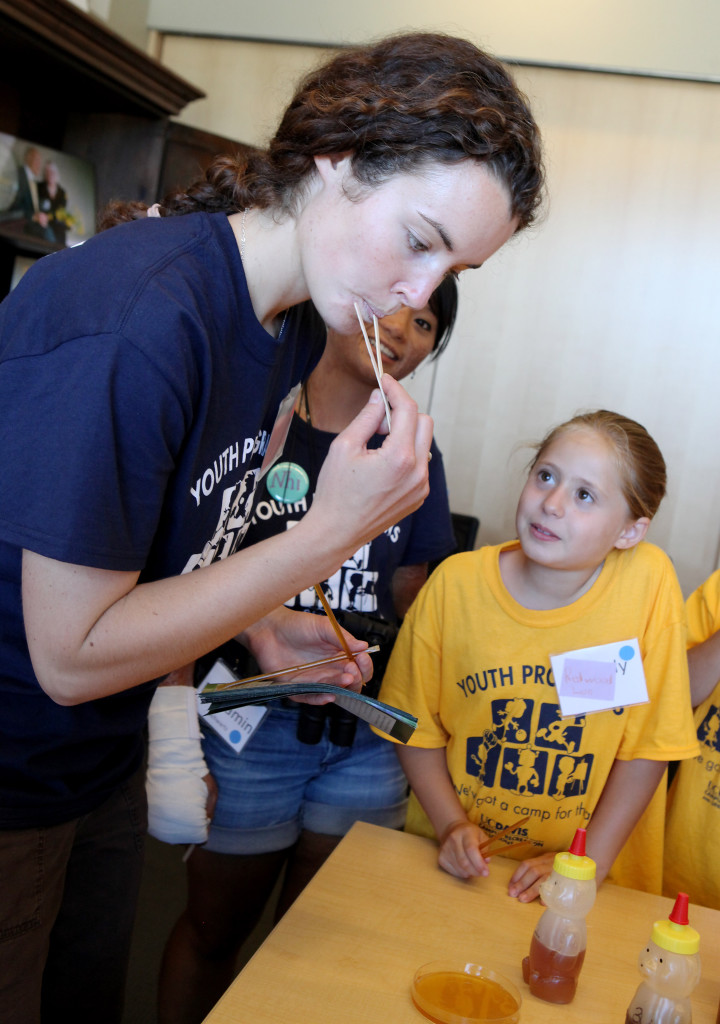 Nicole Westbrook, counselor for a UC Davis youth camp, tastes some honey at the Honey and Pollination Center, as camp participant Cassidy Boynton looks on. Sue Cockrell/Enterprise photo