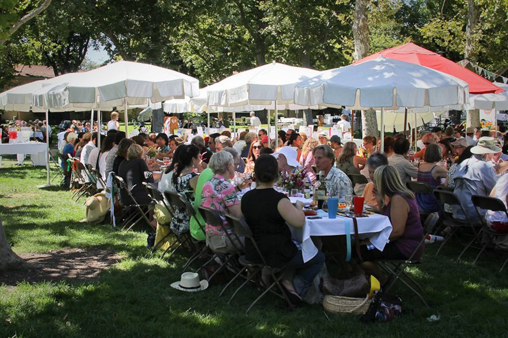 "Village Feast guests enjoy lunch at linen-draped tables under umbrellas and shade trees in Davis' Central Park. The feast is modeled after ""Le Grand Aioli,"" the food lovefest that is a summer tradition in Provence, France. Courtesy photo"