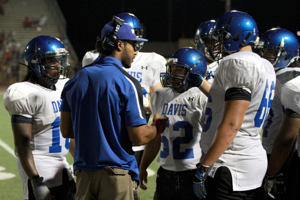 DHS coach Josh Reese goes over strategy with Blue Devil players — from left, Marvin Grant, Marcos Herrera and Bailey Murray — in Friday's loss at Yuba City. Wayne Tilcock/Enterprise photo
